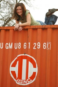 Ashlee Holloway climbs a cargo container to find an angle and to pose.