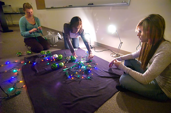 Shayla Sutton, Debbie Liljequist and Devon Liljequist work to light holiday decorations.