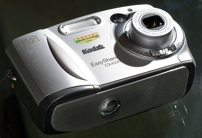My father's Kodak CX4230 digital camera, with add-on aluminum base plate to hold the broken battery door closed.