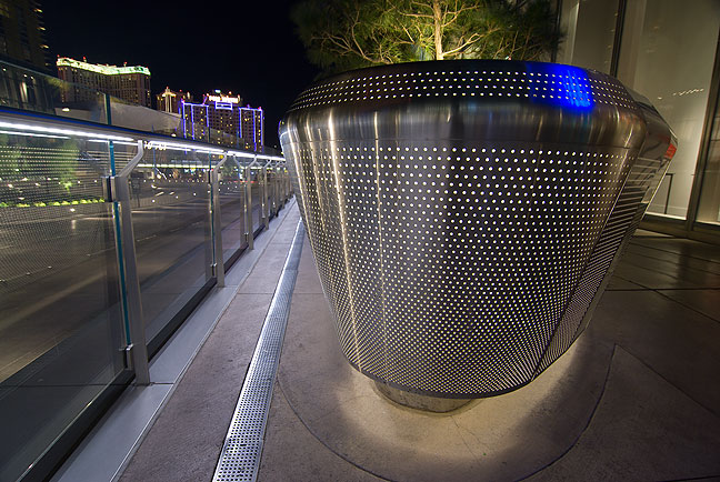 I spotted this elegant stainless steel planter along a sidewalk at City Center in Las Vegas. Note how the lines from the glass rail on the left side guide to eye to the casino lights in the distance.