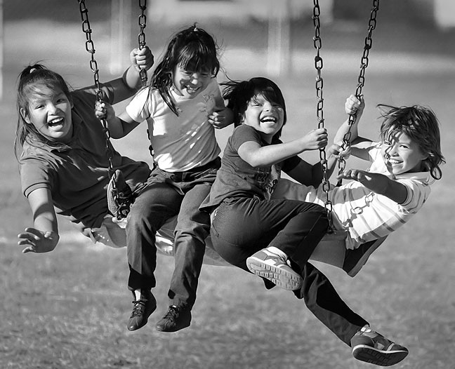 Girls play on a swing set at Hayes School, 1988