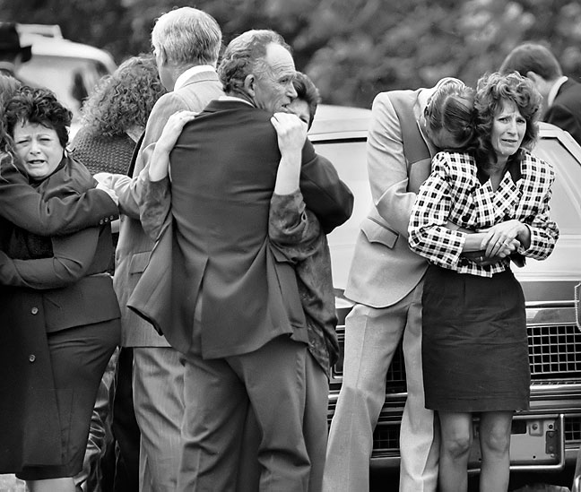 Relatives in a funeral procession grieve after the line of cars was struck head on by another vehicle, killing all of its occupants, 1992