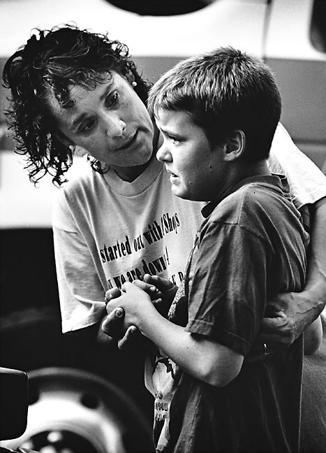 A neighbor comforts a boy after the boy's mother was involved in an injury accident, 1994