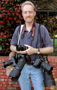 My girlfriend (later, wife) Abby made this image of me in 2003, showing an assortment of cameras I use in my photojournalism.