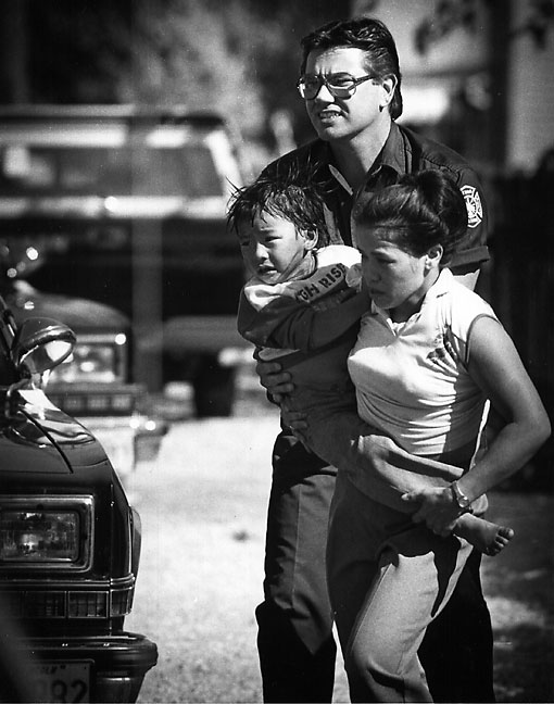 A police officer and a woman rush the woman's son to an ambulance after the child was found in an abandoned refrigerator, 1988