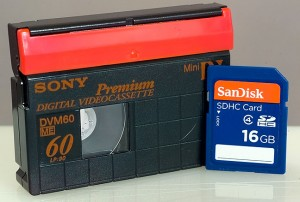 A 60-minute Mini-DV cassette and a 16GB SDHC card; the cassette is awkward and fragile, and there are no larger capacity cassette. At about 200MB per minute, the storage capacity of a DV tape is about 12GB. The SD card is much smaller, has no moving parts, and is available in many different and larger capacities.