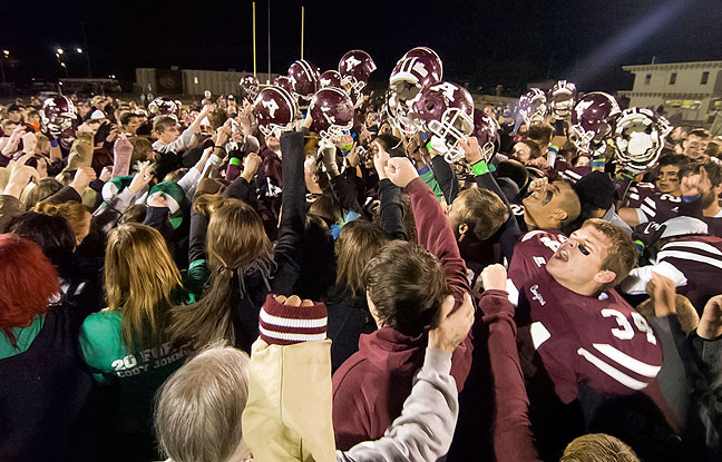 One excellent use for a wide angle lens is to utilize the directional elements of an image, called leading lines, to draw the viewer into the center of an image, as in this November 2012 high school playoff football game.