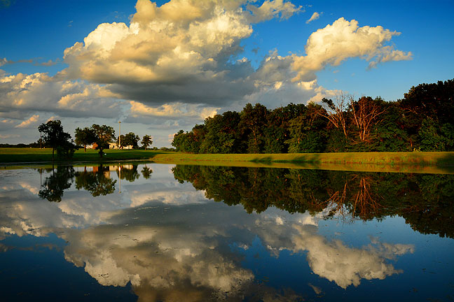 Beautiful cumulus congestus clouds reflect in the pond at the Pontotoc Technology Center last night.