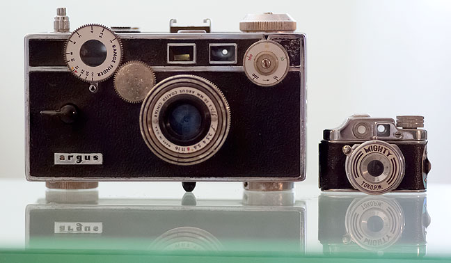 An Argus C3 camera, popular in the 1940s, 1950s, and 1960s, sits next to a quintessentially compact camera, the Toko P.W. Mighty.