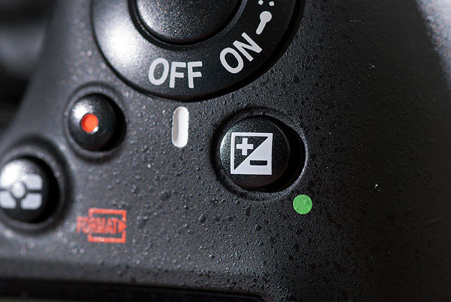 This is the exposure compensation button on a Nikon camera. Different camera companies put it in different places, or embedded in menus, but they all work the same way: letting us fine tune the brightness values of our images. (Don't mistake this for a similar-looking control near the viewfinder, which is the diopter setting.)
