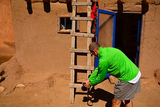 A photographer makes a low-angle shot looking up a ladder at New Mexico's Taos Pueblo in October 2014.