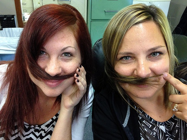 "These are my coworkers Dejah Shea and Ladawna Fry, doing this thing they do absent mindedly sometimes. When I see them doing it, I call it ""mustaching."" Like a lot of my coworkers, I consider them my friends."