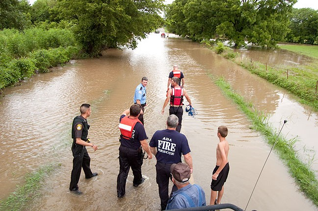 Firefighters and police officers prepare to rescue a man who was wash downstream in floodwaters a few days ago near Stonewall, Oklahoma. I made this image from atop a flatbed truck.