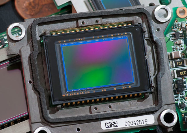 "At the heart of every digital camera is one of these: an integrated circuit with tiny picture elements - ""pixels"" - that record light. Most have filters like anti-aliasing and infrared filters, and most have a Bayer Pattern Array filter. This is the modern equivalent of film."