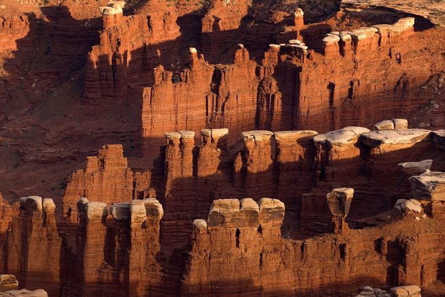Evening sun strikes sandstone pillars in Monument Basic, a dominant feature at Canyonlands National Park.