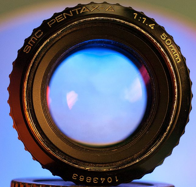 Blue light shines through a big, old Pentax K-Mount 50mm f/1.4 lens.