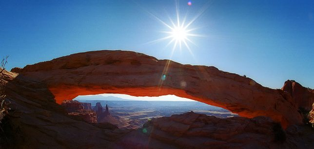 Mesa Arch at Canyonlands is illuminated by handsome morning light in this 2002 image. The light bounces up from canyons below to causing the underside of the arch to take on a deep red. In the distance are the La Sal Mountains.