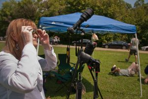 Abby uses her eclipse glasses to peek at the last crescent of the sun as the totality approaches. Behind her is my camera with my 400mm + TC-14 teleconverter.
