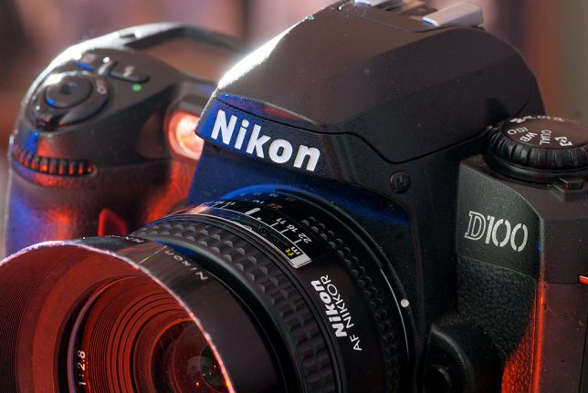 "The D100 has Nikon's classic good looks, and features a magnesium alloy chassis to make it lighter and stronger. Note the ""D100"" logo in the military stencil style."
