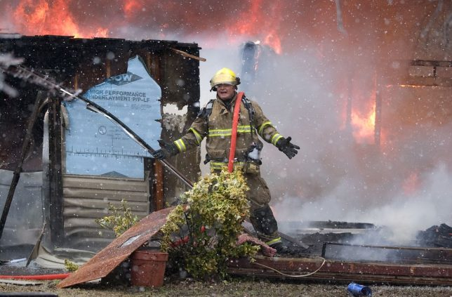 Not all news is good, as in this image of a firefighter frustrated that he can't get water to his hose during a snowstorm at the scene of a fatality house fire north of Ada in January 2010.