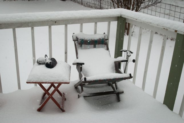 Fresh snow blankets furniture on our front porch this morning.