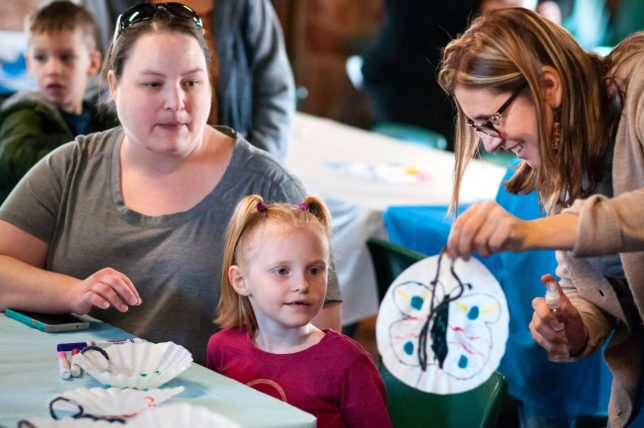 Rebecca Thrailkill, Jayden Janda, and Maria Ruiz-Blanco look at a finished butterfly craft during the Ada Art's Council's Cozy Up with the Arts Sunday, Jan. 26, 2020 at Wintersmith Lodge.