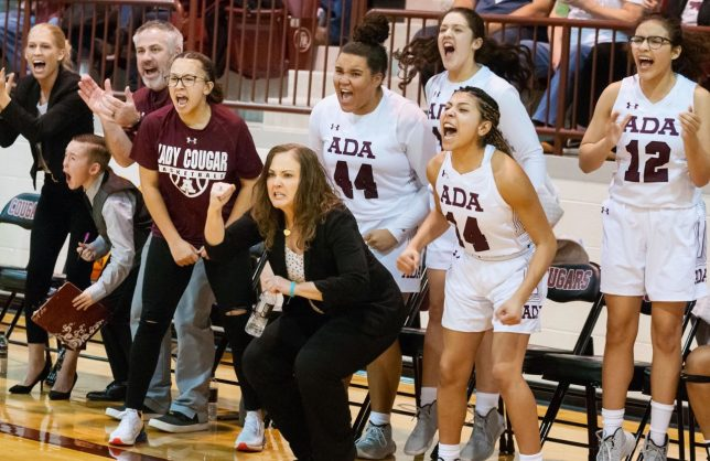 Ada head basketball coach Christie Jennings and her team cheer as their Lady Cougars fight for a chance to stay alive in regional playoffs last month.