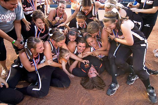 Coach Jennifer Matthews was mobbed by her players celebrating their championship victory, reenacting a similar pile when they won the fast-pitch championship in 2007