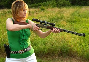 Abby takes aim with her Winchester .22 magnum rifle; the scope is a 3x-9x zoom; note the Walther P22 on her side.
