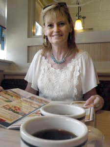 Abby smiles over hot coffee as she looks over the menu at IHOP in Shawnee today.