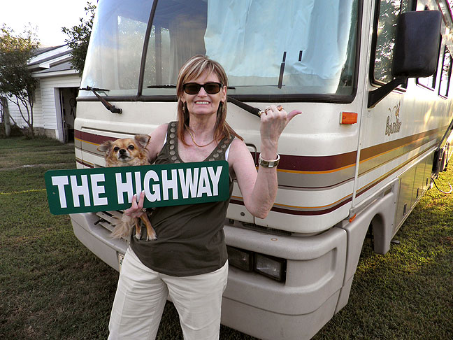 "Abby holds a ""The Highway"" sign we found in one of the numerous storage lockers in the RV; she speculated that the previous owners may have bought it at a flea market or gotten it as a gift."