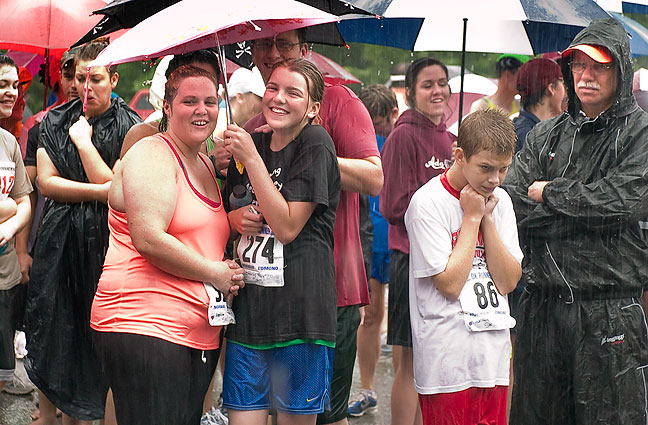 Spectators brave the drenching rain during the Fireball Classic awards presentation this morning in Ada's Wintersmith Park.