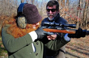 Nicole aims downrange while Bill gives her some pointers.