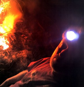 With fruit tree branches and last year's tomato vines burning behind me, I appear ghostly wearing my headlamp.