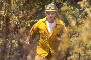A Byng firefighter totes a hose through the woods behind our west pasture yesterday afternoon.