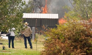 "More than a dozen firefighting agencies were summonded to fight a fire in the Happyland area Saturday afternoon, August 20, 2011. Of note is the fact that the couple in this image is watching fire that is consuming ""ladder fuels,"" brush and grass that surround structures."