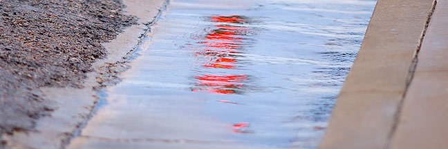 A red traffic light shines on water as it runs off a downtown Ada street this morning. According to Mesonet.org, we received 3.38 inches of rain in the past three days.