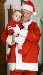 With no need of a false beard due to my own greying, I hold Paul dressed as the jolly elf Santa Claus. I haven't dressed as Santa since I was in the sixth grade Christmas play. Then, as now, I required a pillow to make me look fat enough.