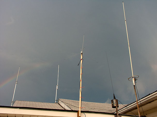 This is my antenna farm with a rainbow behind it. The antennas are, from left to right: Cushcraft Ringo Ranger AR-2 2-meter, Comet GP-1 dual-band 2-meter/70-centimeter, Radio Shack scanner antenna, a 5/8th-wave magnetic mount 2-meter antenna stuck on a coffee can, and my Ringo Ranger AR-6 6-meter.