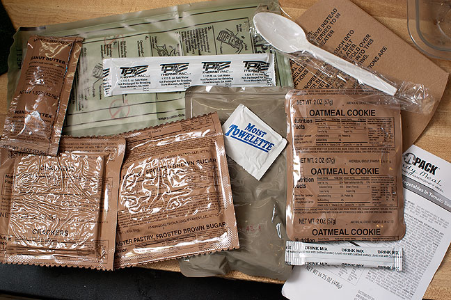The contents of this MRE: pasta with garden vegetables in tomato sauce entreé, oatmeal cookie, frosted brown sugar toaster pastry, peanut butter, cracker, lemonade drink mix, spoon, towelette, heating pouch, and salt water for heater.