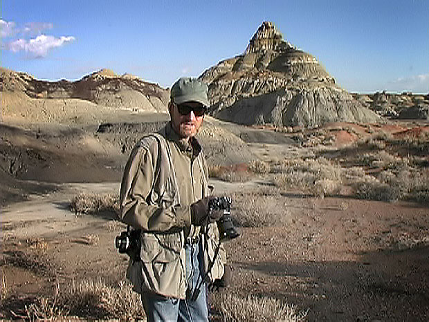 "David Martin made this image of me exploring the Bisti Wilderness, New Mexico, in November 2001. I have only been to Bisti twice, and I have never seen the adjoining De-Na-Zin Wilderness, so it is near the top of my ""next"" list. Photographers note: I am carrying one camera (in my right hand) with black-and-white film with the 25-50mm f/4 Nikkor of 1978 vintage with a deep yellow filter on it, and a camera with color film (hanging from my shoulder) with the 28mm f/3.5 Nikkor and a polarizer. I sold both cameras and lenses long ago."