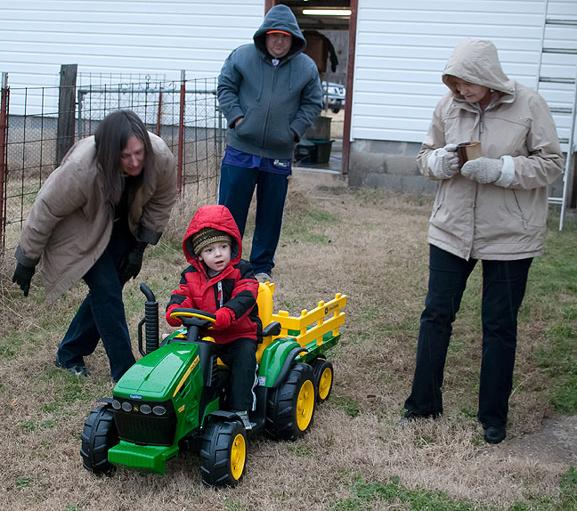 Flanked by Chele, Tom and Abby, Paul rides his new toy lawn tractor in our back yard in freezing rain. Tom helped me assemble it, and we found it to be put together in much the same way as our real John Deere lawn tractor.
