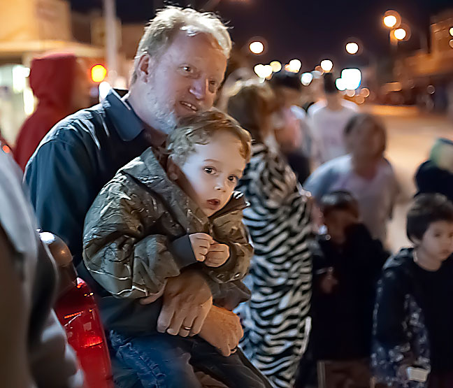 Abby made this image of me holding Paul at tonight's parade. His jacket is a Christmas present from us.