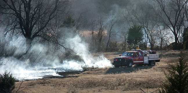 A grass rig from the Byng Fire Department works to put out a wildfire just down the street from our house.