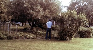 Our father, Joe Barron, looks over his mother's garden in Independence, Missouri, in about 1976. Visible are rows of planted crops, as well as the large apple tree at the back of the garden.