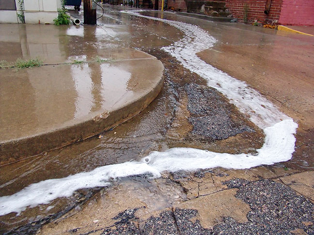 Rainwater runoff makes rivulets on a downtown street this morning.