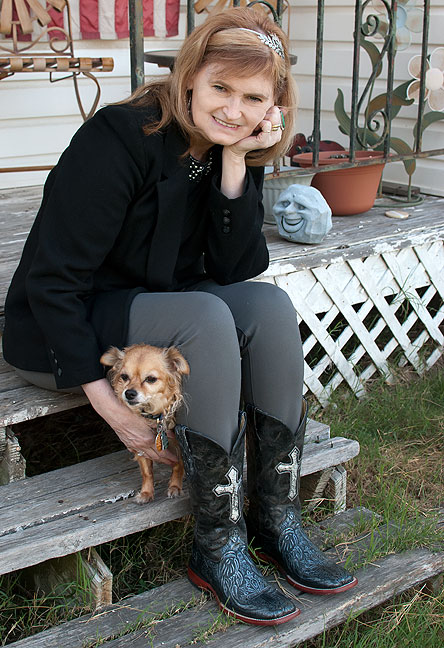 Abby poses on our front porch tonight, petting her Chihuahua Sierra and wearing her black boots.