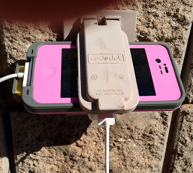 Despite having some disdain for people who behave like zombies staring at their phones, I did find this method of storing/charging a phone in an outdoor plug at a softball game to be a fairly creative deployment.