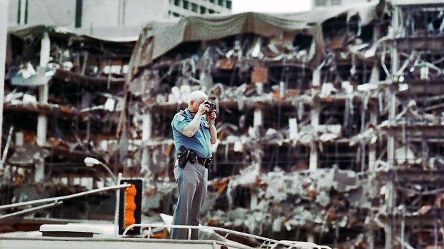 A police officer takes a picture from atop an emergency command vehicle with the bombed Alfred P. Murrah Federal Building in the background.