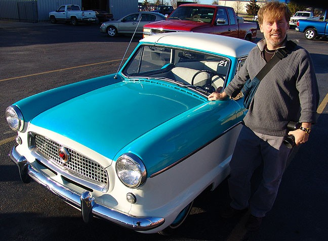 R. E. poses with a Nash Metropolitan, his dream car, several years ago,